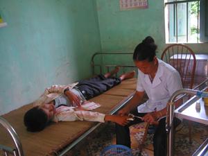 Cán bộ Trạm y tế xã Mường Chiềng (Đà Bắc) băng bó, điều trị cho nạn nhân bị thương tích do bất cẩn trong sử dụng công cụ sản xuất nông nghiệp.
