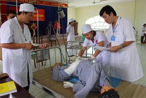 Ban giám khảo chấm điểm phần thi thực hành chăm sóc bệnh nhân trên mô hình.
