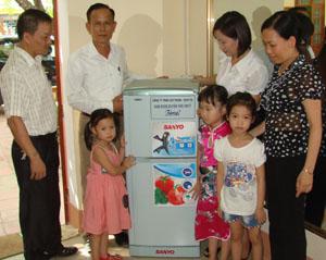 Ông Hoàng Công Đoài (người đứng giữa) và lãnh đạo  Phòng GD&ĐT huyện trong buổi tặng tủ lạnh cho cô, trò  trường mầm non Sơn Ca, thị trấn Hàng Trạm (Yên Thủy).