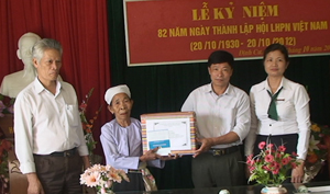 Đại diện Ban Tuyên giáo Huyện ủy, Ngân hàng NN&PTNT, Hội cựu TNXP huyện Lạc Sơn tặng xổ tiết kiệm cho nữ cựu TNXP Bùi Thị Bù, xóm Đôm, xã Đinh Cư.
