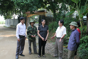 Ông Đinh Ý Quỳnh (đứng thứ ba từ phải sang) đang trò chuyện cùng người dân trong xóm trên con đường do gia đình ủng hộ cát, sỏi, ngày công san lấp mặt bằng.