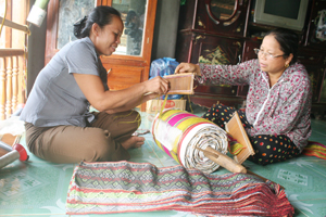 Chị Dương Thị Bin (bên trái) và chị Bùi Thị Lán nhặt hoa văn,  mắc khung dệt để giao cho người lao động.