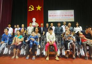 Đại diện Quỹ Bảo trợ trẻ em, tổ chức Vietnam Outreach (Australia), Sở LĐ, TB & XH trao xe lăn cho trẻ em tại huyện Tân Lạc.