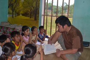 Anh Bùi Văn Bình ôn tập bài cho các em học sinh lớp 4.