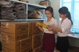 Cán bộ Trung tâm DS/KHHGĐ huyện Lạc Thủy kiểm tra tài liệu truyền thông trước khi cấp phát cho các xã, thị trấn. Ảnh: Hồng Nhung.