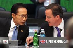 Tổng thống Hàn Quốc Lee Myung-bak và Thủ tướng Anh David Cameron (từ trái sang phải) đã cố gắng giảm bớt bất đồng trong vấn đề tỷ giá và thương mại tại phiên họp toàn thể của Hội nghị G20.