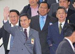 Ông Vejjajiva vẫy chào khi ra khỏi tòa ở Bangkok