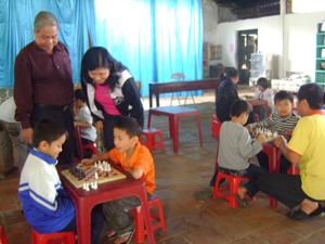 Học sinh lớp cờ vua được thực hành dưới sự hướng dẫn của huấn luyện viên.