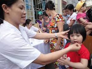 Cán bộ Trạm y tế phường Hữu Nghị (TPHB) cho trẻ uống vitamin A.