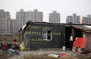 Một người dân nhập cư đứng bên căn nhà tạm bợ của mình ở Thượng Hải - Ảnh: Reuters
