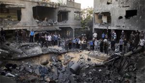 Người dân Palestine đứng quanh một hố bom sau cuộc không kích của Israel - Ảnh: CNN