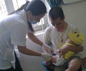 Cán bộ y tế phường Hữu Nghị (TPHB) tiêm vacxin Quinvaxem cho trẻ trong đợt tiêm ngừa trở lại ngày 5/11.