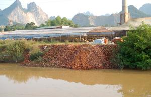 Dòng sông Bùi, đoạn qua thị trấn Lương Sơn bị ô nhiễm vì dòng nước thải của các DN sản xuất vật liệu xây dựng trên địa bàn.