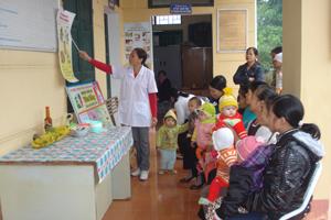Cán bộ Trạm Y tế xã Dân Chủ tư vấn nấu cháo dinh dưỡng, chăm sóc sức khỏe ban đầu cho trẻ.