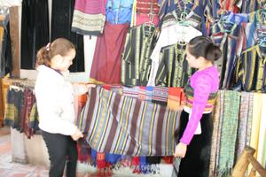 Chị Vì Thị Mai (phải) Bản Lác giới thiệu sản phẩm dệt thổ cẩm.