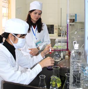 Chị Trần Thị ái Hương (người đứng) kiểm tra, giám sát xét nghiệm tại Labo xét nghiệm Trung tâm Y tế Dự phòng tỉnh.