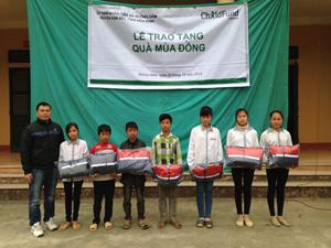 Đại diện tổ chức Childfund Việt Nam trao áo khoác cho trẻ em xã Nuông Dăm.