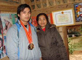 Nhà vô địch quốc gia Đinh Thế Bình bên mẹ cùng tấm huy chương vàng toàn quốc.