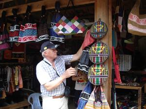 Khách du lịch nước ngoài thích thú với những sản phẩm lưu niệm còn giữ nguyên bản sắc dân tộc được người dân bản Giang Mỗ (Cao Phong) làm ra và bày bán ngay tại nhà