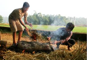 """Người Mường Vang vẫn giữ phong tục tập quán  """"Cơm đồ, nhà gác, nước vác, lợn thui"""". Trong ảnh: Lợn được đem thui trước khi đem chia phần cho các nhà ăn đụng."""