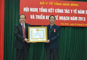 Thừa ủy quyền, lãnh đạo Sở Y tế trao Huân chương Lao động hạng ba cho đồng chí Giám đốc Bệnh viện đa khoa huyện Kim Bôi.