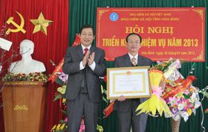 Thừa ủy quyền của Chủ tịch nước, đồng chí Bùi Văn Cửu, Phó Chủ tịch TT UBND tỉnh trao Huân chương Lao động hạng ba cho đồng chí Bùi Văn Tuyến, Phó Giám đốc BHXH tỉnh.