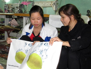 Chị Quách Thị Như hướng dẫn công nhân hoàn thiện sản phẩm túi siêu thị.