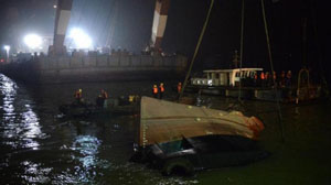 Các nhân viên cứu hộ đang tìm cách nâng con tàu bị chìm khỏi mặt nước. (Ảnh: Xinhua)