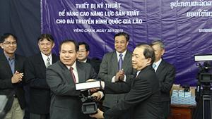 Phó Tổng Giám đốc Đài THVN Trần Dũng Trình (bên phải) trao tặng thiết bị cho Tổng Giám đốc Đài THQG Lào Bun-chao Phi-chít.