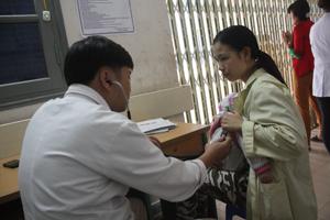 Bác sĩ Đặng Thành Chung, Phó trưởng Khoa Nhi, Bệnh viện đa khoa tỉnh khám bệnh cho trẻ em.