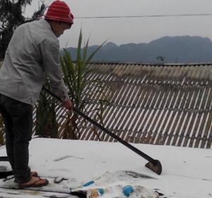 Nhân dân xóm Lài, xã Đồng Nghê dọn băng tuyết trên mái nhà.