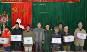 Đại diện lãnh đạo Trung tâm DN&VL - Bộ CHQS tỉnh tặng quà cho các hộ gia đình chính sách xã Mường Chiềng.