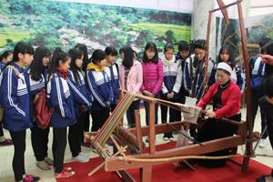Các em học sinh trường THPT Công nghiệp tham quan, tìm hiểu nghề dệt vải truyền thống của người Mường.