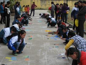Học sinh THCS vẽ tranh trên nền xi măng.