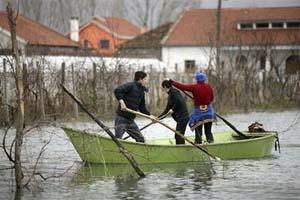 Người dân trong làng Obot, gần thành phố Shkodra, Albani chèo thuyền trong nước lũ vào ngày 10/1. Các nhà khoa học cảnh báo lũ lụt và hạn hán sẽ tăng khi trái đất ấm lên. Ảnh: AP.