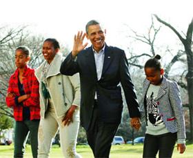 Ông Obama cùng vợ và hai con gái đi dạo phố.