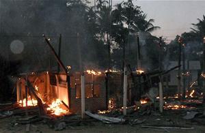 Một ngôi nhà của người dân Thái Lan bị cháy vì đạn pháo.