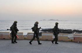 Các binh sĩ Hàn Quốc đi tuần trên đảo Yeonpyeong, nơi trúng pháo của Triều Tiên trong vụ đấu pháo hôm 23/11/2010.