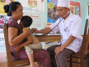 Cán bộ y tế xã khám bệnh cho trẻ dưới 6 tuổi tại trạm y tế.