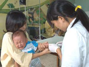 Cán bộ y tế cần kiểm tra kỹ hạn sử dụng của vaccin khi tiêm phòng cho trẻ.