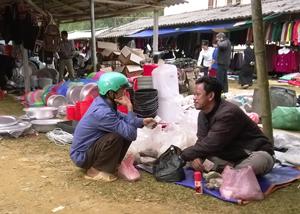 """""""Thầy thuốc""""  (ngồi bên phải) giới thiệu là người Chăm, quê ở Ninh Thuận đang chẩn đoán và kê đơn thuốc cho một người bệnh tại chợ Lỗ Sơn."""