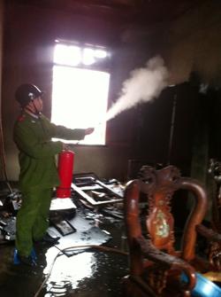 Lực lượng Công an huyện Yên Thủy huy động bình chữa cháy xách tay dập tắt ngọn lửa.