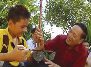 Ông Đinh Văn Tỉnh, xóm Đon, xã Mỹ Hòa (Tân Lạc) truyền đạt cách sử dụng nhạc cụ dân tộc cho thế hệ trẻ.