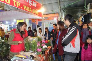 Người dân đến ủng hộ gian hàng gây quỹ từ thiện của Đội tình nguyện Áo đỏ