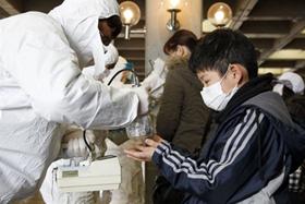 Chuyên gia y tế kiểm tra nồng độ phóng xạ cho người dân sống gần nhà máy điện hạt nhân Fukushima Dai-ichi tại một trại sơ tán ở thành phố Koriyama, tỉnh Fukushima vào ngày 16/3