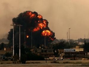 Khói lửa bốc lên sau khi máy bay ném bom của Libya bị bắn rơi ngày 19/3.