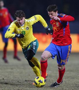 Tiền vệ Xabi Alonso (áo đỏ) tranh bóng với một cầu thủ chủ nhà.