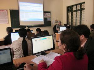 Cán bộ quản lý các trường tiểu học thực hành phần mềm Smas2.0 trên máy tính có tài liệu hỗ trợ và giảng viên CNTT hướng dẫn.