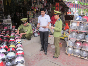 Cán bộ Đội QLTT số 1 tuyên truyền, phổ biến Thông tư 06/2013 và hướng dẫn về quy chuẩn kỹ thuật Quốc gia tới hộ kinh doanh mũ bảo hiểm chợ Phương Lâm (TPHB).