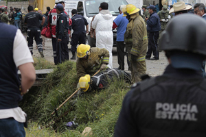 Nhân viên cứu hộ tìm kiếm tử thi dưới một mương tại hiện trường vụ nổ hôm 16/3. Ảnh: AP.